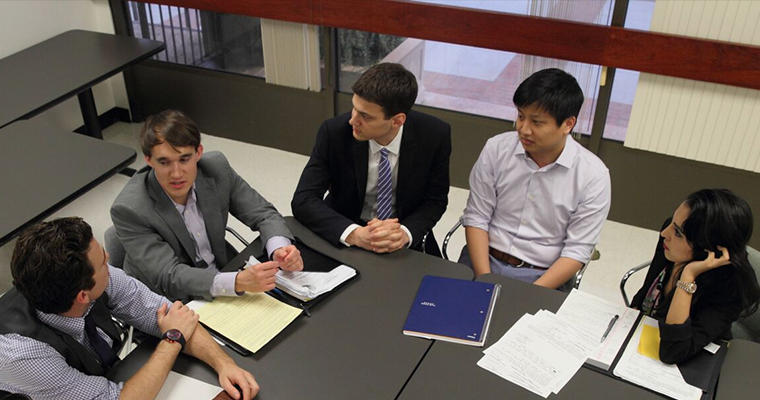 A group of USC Gould students having a discussion in a classroom for their Compliance Certificate