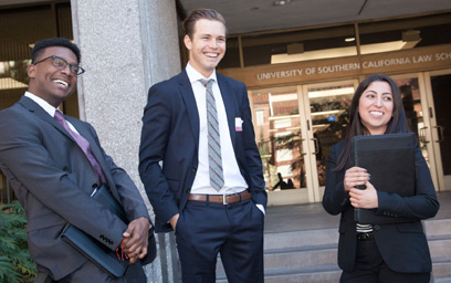 Three USC Gould students standing in front of the USC Law School building