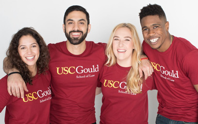 A group of 4 USC Gould students smiling while wearing USC Gould t-shirts